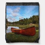 Red canoe on lake bank drawstring bags