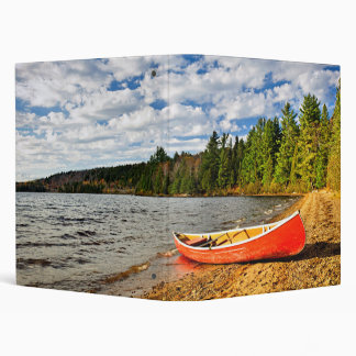 Red canoe on lake shore binder
