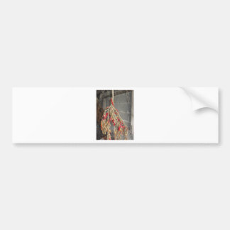 Red chili peppers hanging to dry on brick wall bumper sticker