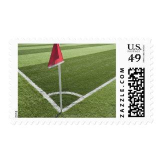 Red corner flag on soccer field postage