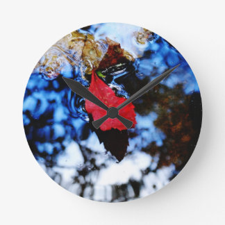 Red floating fall leaf with reflection of blue sky round wallclocks