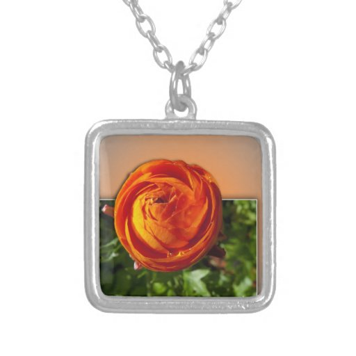 Red flower coming out of frame with a hint of yell necklace