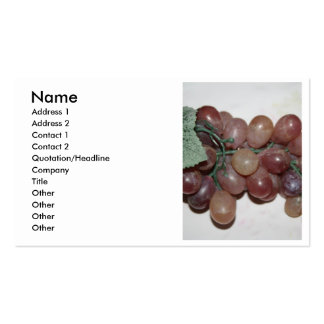 Red grapes, plastic, on pale background business card