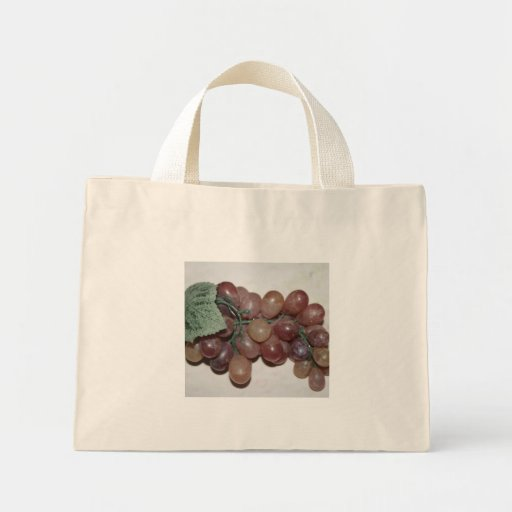 Red grapes, plastic, on pale background tote bags