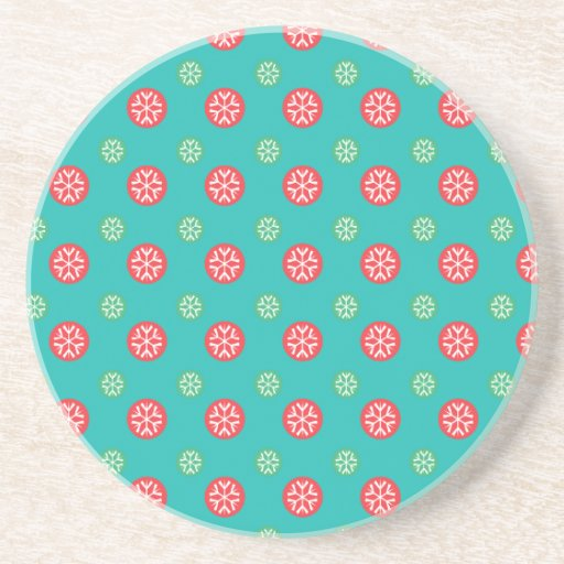 Red green snowflakes in circles on turquoise drink coasters