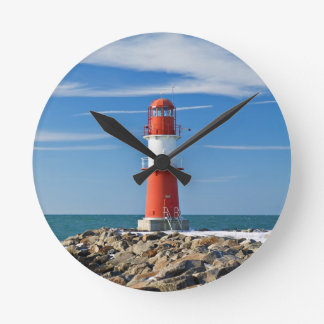 Red lighthouse with blue sky round wall clocks