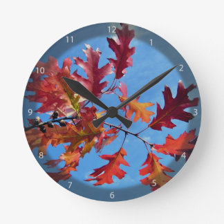 Red maple leaves against blue sky round wallclock