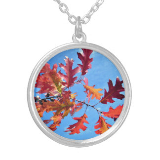 Red maple leaves against blue sky round pendant necklace