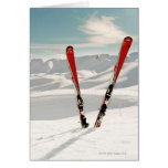 Red pair of ski standing in snow greeting card