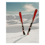 Red pair of ski standing in snow poster