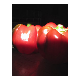 Red peppers illuminated by sunshine in the dark letterhead