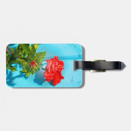 red rose against blue plastic wrap style tag for luggage
