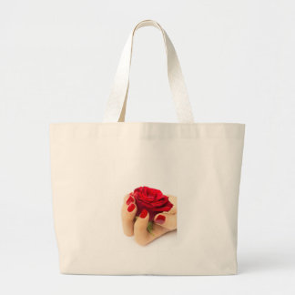 Red rose in female hand large tote bag