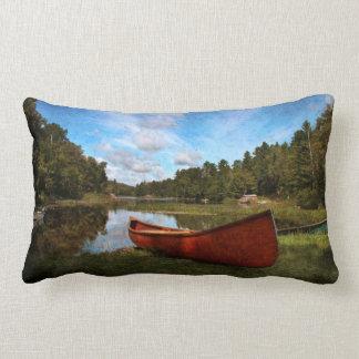 Red rustic canoe on a lake bank lumbar pillow