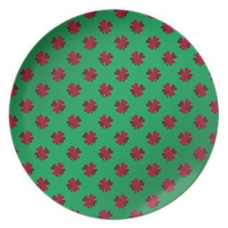 Red shamrocks on green background plates