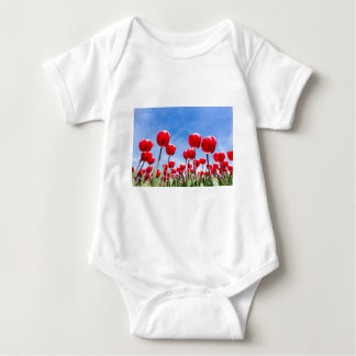 Red tulips field from below with blue sky baby bodysuit