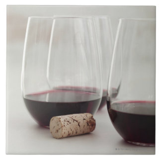 Red wine in stemless glasses large square tile