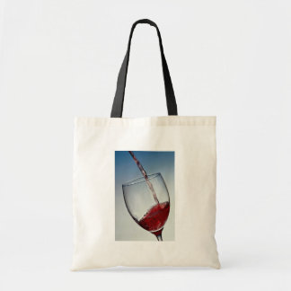 Red wine poured into wine glass tote bag