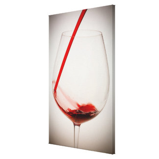Red wine pouring into glass, close-up canvas print