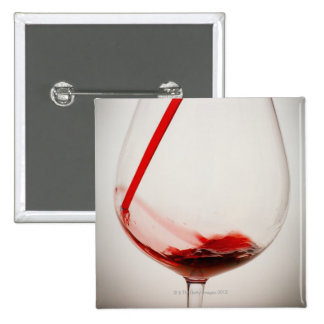 Red wine pouring into glass, close-up pinback button