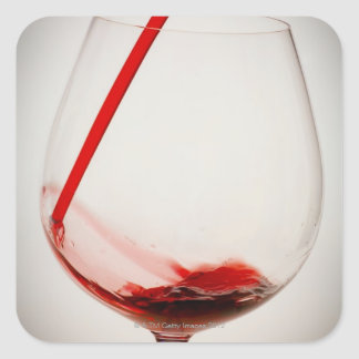 Red wine pouring into glass, close-up square sticker
