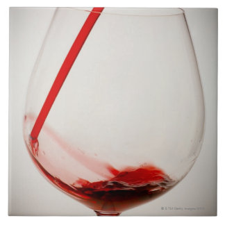 Red wine pouring into glass, close-up large square tile