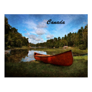 Red wooden canoe on the bank of a lake post card