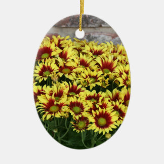 Red Yellow Flowers against brown red brick wall Double-Sided Oval Ceramic Christmas Ornament