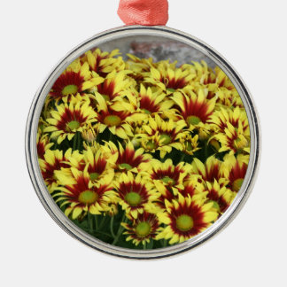 Red Yellow Flowers against brown red brick wall Round Metal Christmas Ornament