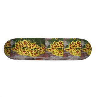 Red Yellow Flowers against brown red brick wall Skateboard Deck