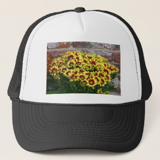 Red Yellow Flowers against brown red brick wall Trucker Hat