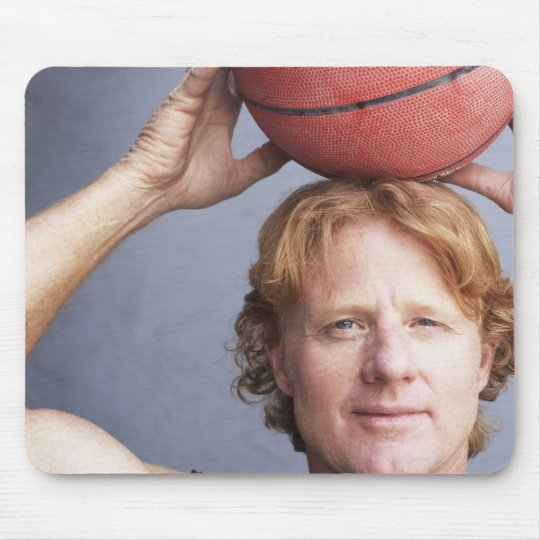 Redhead holding a basket ball over his head mouse pad