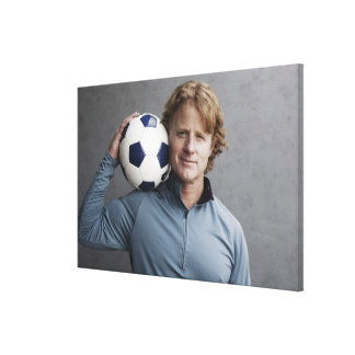 Redhead holding a soccer ball on his shoulder canvas print