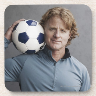Redhead holding a soccer ball on his shoulder drink coaster