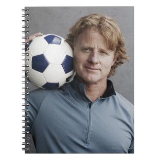 Redhead que sostiene un balón de fútbol en su homb libros de apuntes