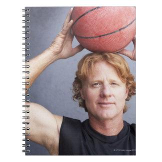 Redhead que sostiene una bola de la cesta sobre su libretas