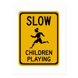 Reduzca - a los niños que juegan, señal de peligro postal