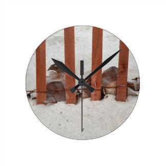 redwood fence sea grape leaves sand image round clock