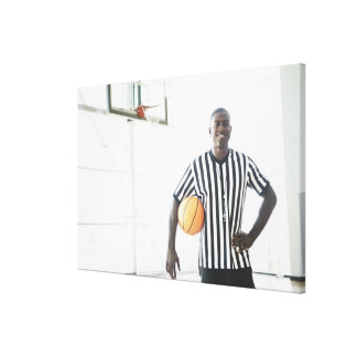 Referee holding basketball on court canvas print