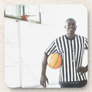 Referee holding basketball on court drink coaster