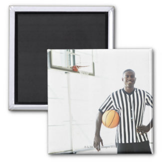 Referee holding basketball on court magnet