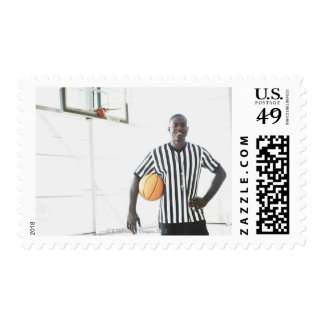 Referee holding basketball on court postage