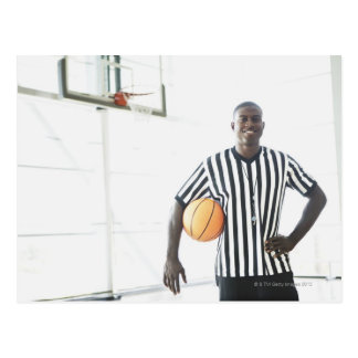 Referee holding basketball on court postcard