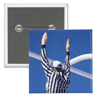 Referee signaling touchdown or successful field pins