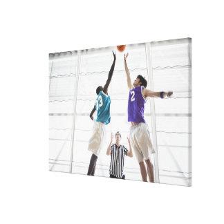 Referee watching basketball players jumping canvas print