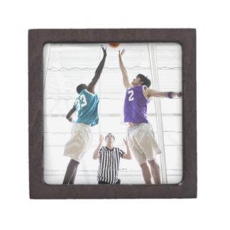 Referee watching basketball players jumping gift box