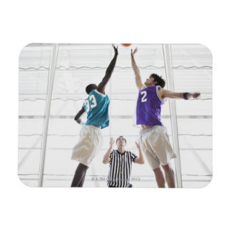 Referee watching basketball players jumping magnet