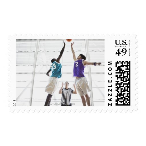 Referee watching basketball players jumping postage stamp
