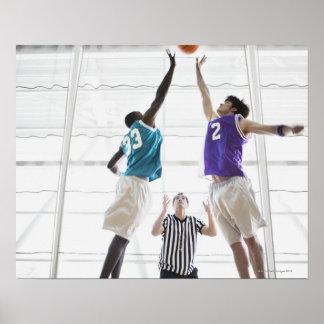 Referee watching basketball players jumping poster