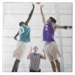 Referee watching basketball players jumping ceramic tile